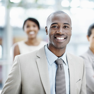 Confident African American businessman stands at his workplace with his colleagues in the background